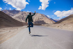 Extremely happy young male tourist jumping on country road with giant mountains behind Stock Photos