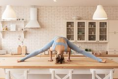 Focused short-haired active yoga master standing on her head on kitchen table royalty free stock images