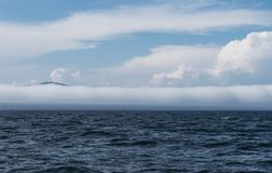 Extremely long barrel cloud covers the coast. The view of a barrell cloud covering the coast of Maine taken from a boat in the ocean stock photography