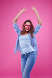 Extremely positive young girl having fun in the studio. Mid shot of young girl having fun isolated over pink background. Female in casual outfit dancing and Stock Image