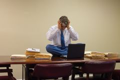 Extremely stressed out upset overworked man at work sitting on table with stacks of project folders Stock Photography