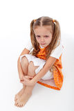 Extremely unhappy little girl sitting. And crying - on white background Royalty Free Stock Photography