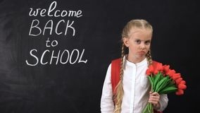 Extremely upset girl with tulips standing near chalkboard, not wanting to school. Stock footage stock footage
