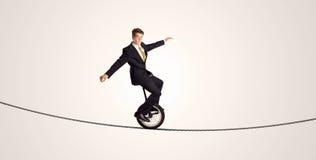 Extremer Geschäftsmann-Reitenunicycle auf einem Seil Stockbild