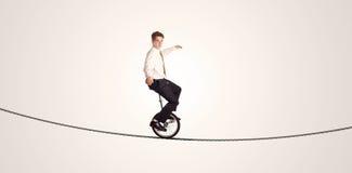Extremer Geschäftsmann-Reitenunicycle auf einem Seil Lizenzfreies Stockbild