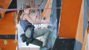 Extremer Sport, bouldering Eine junge Frau, die oben klettert, um eine Hilfe bittet und unten kommt stock video