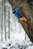 Extremer Wintersport Junger Mann, der einen Felsen mit sichern klettert Seilklettern stockfotos