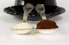Extremes meet. Two  tea-spoon with coffee and sugar infront of cofee-cup Royalty Free Stock Images