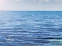 Extremidad de la caña de pescar con la línea saliente en el mar Fotografía de archivo