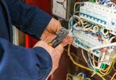 Extremidades de descascamento do eletricista dos fios na placa de distribuição, imagem de stock