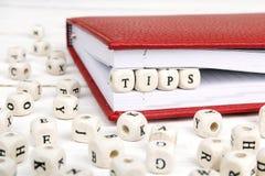 Extremidades de la palabra escritas en bloques de madera en cuaderno rojo en la madera blanca Foto de archivo