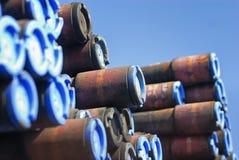 Extremidades de uma pilha de tubulações cobertas com os tampões azuis fotografia de stock