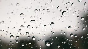 Extremo cercano para arriba de la lluvia en el parabrisas metrajes