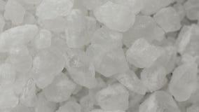 Extremo cercano para arriba de los cristales de la sal del mar que giran almacen de video