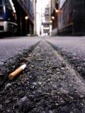 Extremo de cigarrillo en callejón Fotos de archivo libres de regalías