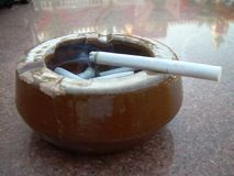 Extremo de cigarrillo que fuma en el cenicero en la tabla de mármol imagen de archivo