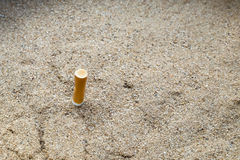 Extremo de cigarrillos en cenicero de la arena Foto de archivo