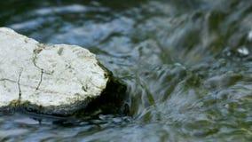 Extremo próximo acima da rocha no córrego da água filme