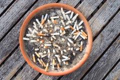 Extremos de cigarrillo en el cenicero en el fondo de madera de la tabla El concepto de mundo ningún día del tabaco en el 31 de ma Fotografía de archivo