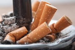 Extremos de cigarrillos en cenicero lleno Fotografía de archivo