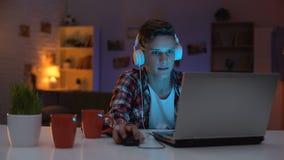 Extremt angelägen tonåring som spelar dataspelen på obehärskade sinnesrörelser för bärbar dator lager videofilmer