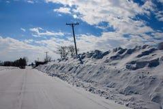 Extremt djupa snowbanks sköt telefonpolen böjde royaltyfri bild