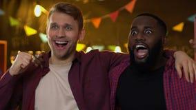 Extremt emotionella manliga fans som firar favorit- seger f?r sportlag i bar arkivfilmer