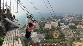 Extremt hopp från det Pattaya stadstornet Kvinnan går ner kabeln från taket stock video