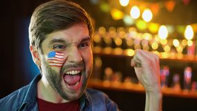 Extremt lycklig amerikansk fotbollfan med flaggan på kinden som ja gör gesten, seger lager videofilmer