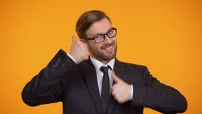 Extremt lycklig kontorsarbetare som visar upp tummar, lyckad investering, avtal arkivfilmer