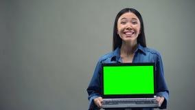 Extremt lycklig kvinnainnehavbärbar dator med den gröna skärmen, stor vinst direktanslutet arkivfilmer