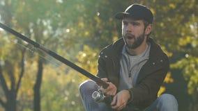 Extremt lycklig manspolningslinje av att fiska rullen som ser fisken, bra meta för lås arkivfilmer
