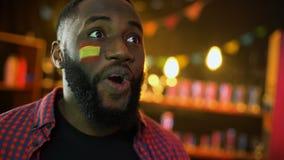 Extremt lycklig svart spansk fan med flaggan på kind som ropar, segra för lag stock video