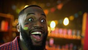Extremt lycklig svart tysk fotbollsfan med flaggan på kinden som firar seger lager videofilmer