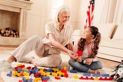 Extremt lyckliga familjemedlemmar som spelar med konstruktionsuppsättningen Arkivbilder
