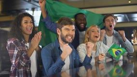 Extremt lyckliga sportfans som vinkar den Brasilien flaggan i service av landslaget arkivfilmer