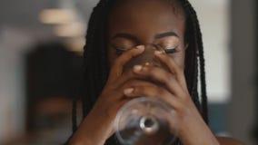 Extremt slut upp av den kvinnliga modemodellen för ung härlig afrikansk amerikan som rymmer den tomma vinglaset i hennes hand och lager videofilmer