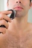 Extremt slut upp av den shirtless mannen som rakar med rakapparaten Arkivfoton