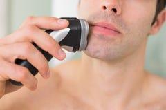 Extremt slut upp av den shirtless mannen som rakar med rakapparaten Royaltyfri Foto