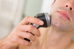Extremt slut upp av mannen som rakar med rakapparaten Royaltyfri Foto