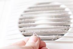 Extremt smutsigt och dammigt vitt plast- hemmastatt slut f?r ventilationsluftskyddsgaller upp och en hand som rymmer damm vid fin arkivfoto