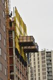 Extrernal frame of new construction. Yellow façade of a Brooklyn building under construction with a crane on the side royalty free stock images