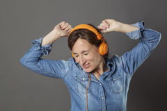 Extrovert beautiful middle aged woman with eyes closed enjoying dancing Stock Photo