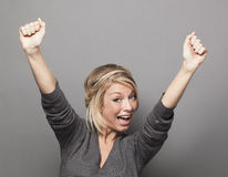 Extrovert 20s blonde woman raising hands for victory Royalty Free Stock Photo