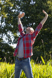 Extrovert 40s man raising his arms up for optimism Stock Images