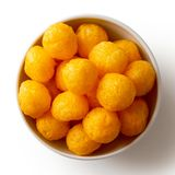 Extruded puffed cheese balls in white ceramic dish isolated on w. Hite from above Royalty Free Stock Photo