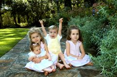 Exuberant Brother. Four siblings sit in the middle of a garden path.  Three sisters and one brother.  One is holding his arms in the air and yelling.  The others Royalty Free Stock Photos