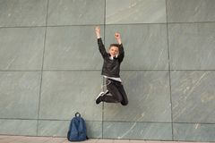 Exuberant energetic young boy jumping. In the air with raised arms in front of a grey stone tiled urban building with copy space Stock Photos