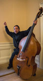 Exuberant excited Asian Musician with his Upright String Bass. Asian man with his arms extended holding his instrument, a String Upright Bass Stock Images