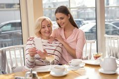 Exuberant granny taking selfies with her granddaughter royalty free stock photography